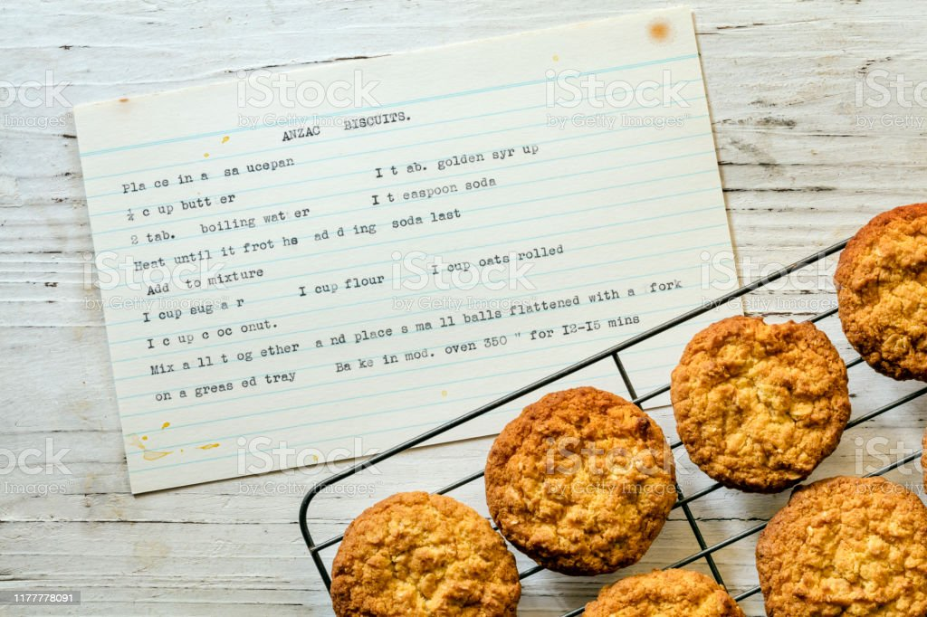 Anzac Biscuits with Vintage Typewritten Recipe Top View Anzac biscuits on rack with vintage typewritten recipe.  Top view on rustic timber. ANZAC Day Stock Photo