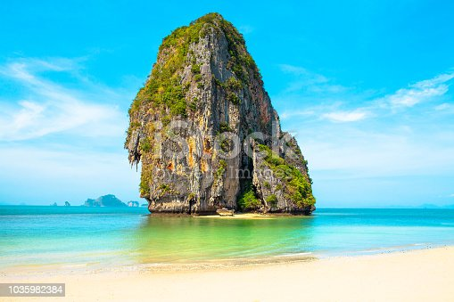 Isolated standalone limestone cliff at Phra Nang beach. Clean white sand and turquoise water. Pristine beach. No people.