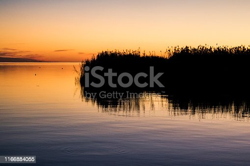 Over the marsh grass the sun is seen setting over Apalachicola Bay, Florida.
