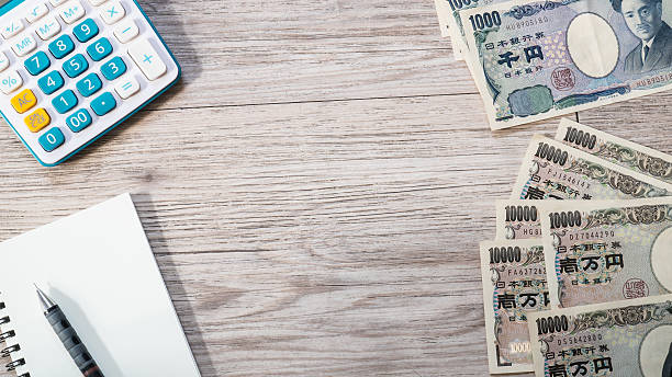 apanese yen currency and Calculator, notebook, pencil on wooden background stock photo