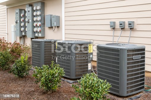 Three air conditioning units with a panel of electricity meters behind, all at the side of a recently-constructed apartment building.  The yellow energy usage stickers are not from the manufacturer, but the U. S. government.