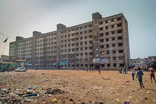 Mumbai, India - January 12, 2015: Unfinished empty apartment block and dirty field with people in Dharavi slum. Dharavi is one of the largest slums in the world.