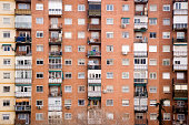 """""""Apartment block with balconies full of various objects, and air conditioners mounted on the walls."""""""