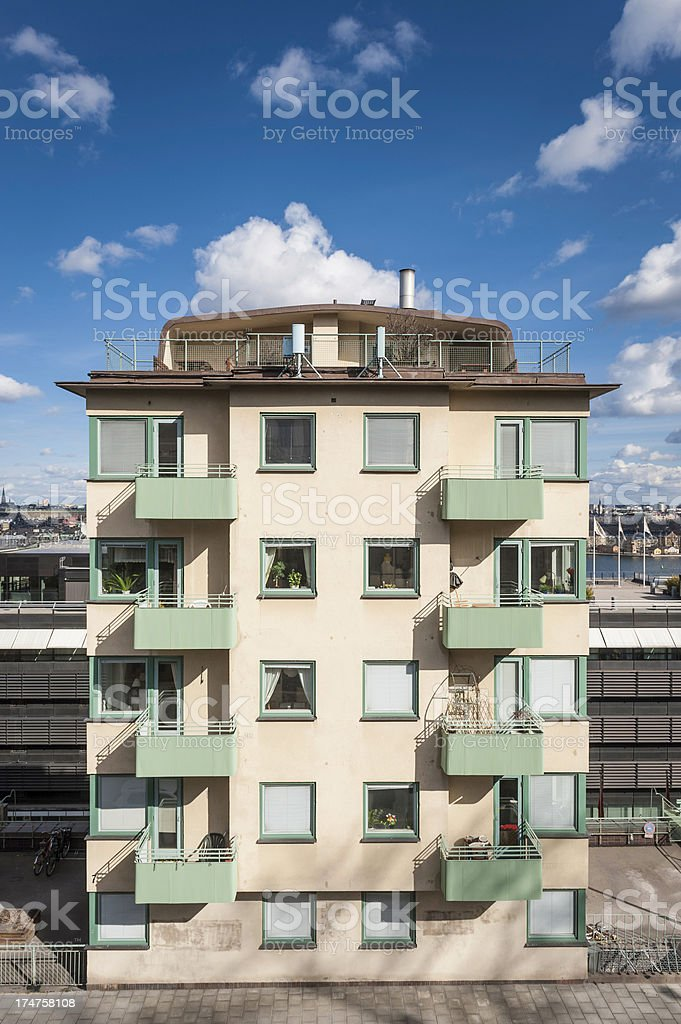 Apartment block with balconies blue skies fluffy clouds royalty-free stock photo