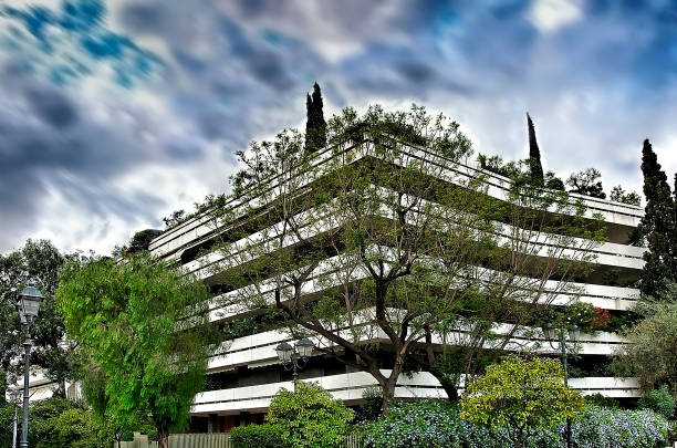 Apartment building n centre of  Athens city with green trees under a dramatic sky in motion. stock photo