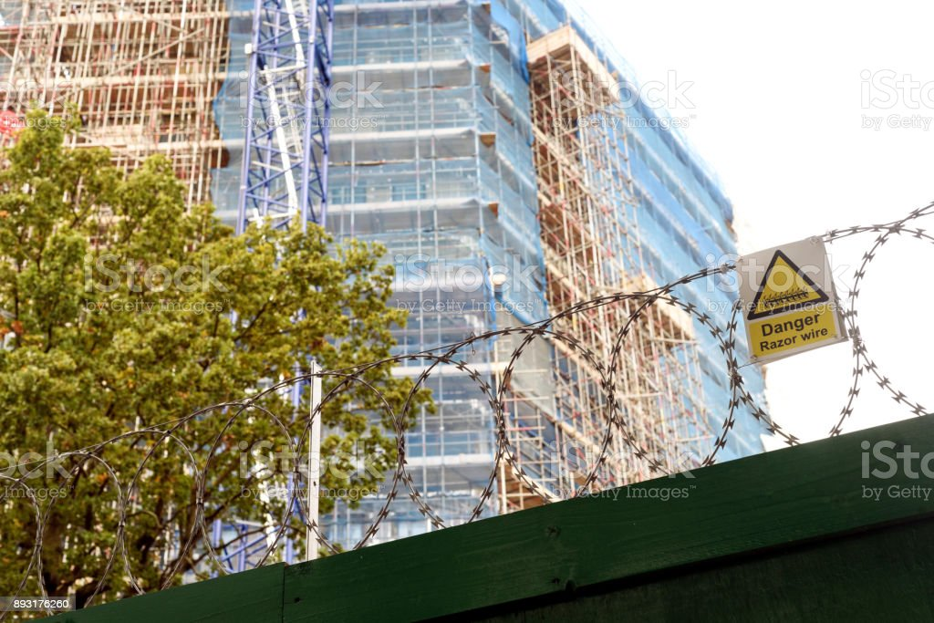 Apartment Building Site and Razor Wire stock photo