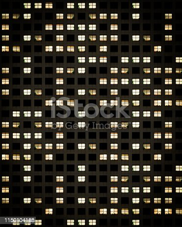 Windows lights in a high-rise apartment building at night.