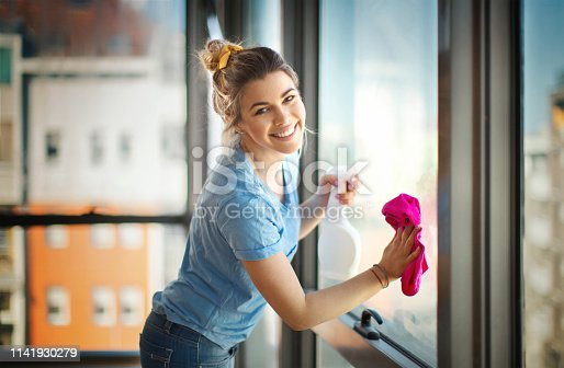 Closeup side view of a young woman cleaning windows in her apartment. She's taking a quick smiling glance at the camera.