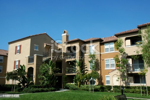 Large three story apartment complex in southern California. Green grass in front and clear blue sky in background.