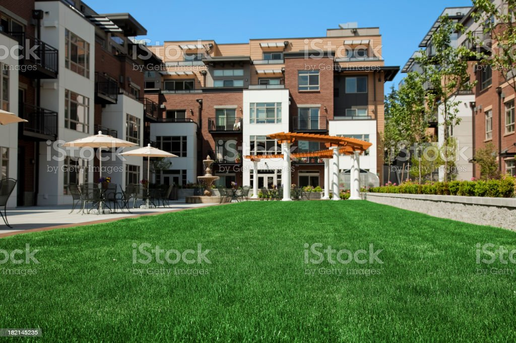 Apartment Condos home courtyard landscaped grass building tables umbrellas stock photo
