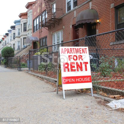 A sandwich board sign on a city street that is advertising an apartment for rent.