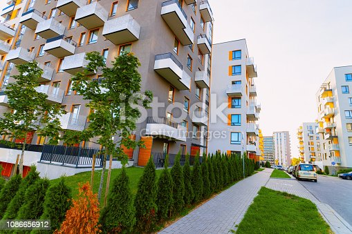 Apartment house residential building complex real estate concept. Street car parking. During the sunset