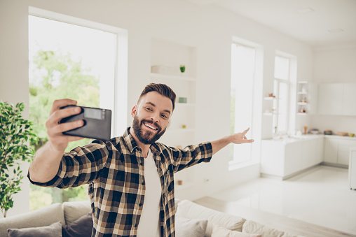 Apartment purchase concept. Let's go and I'll show you my house! Young man make call on front camera of modern smartphone standing in the middle of a light room in his brown stylish trendy shirt