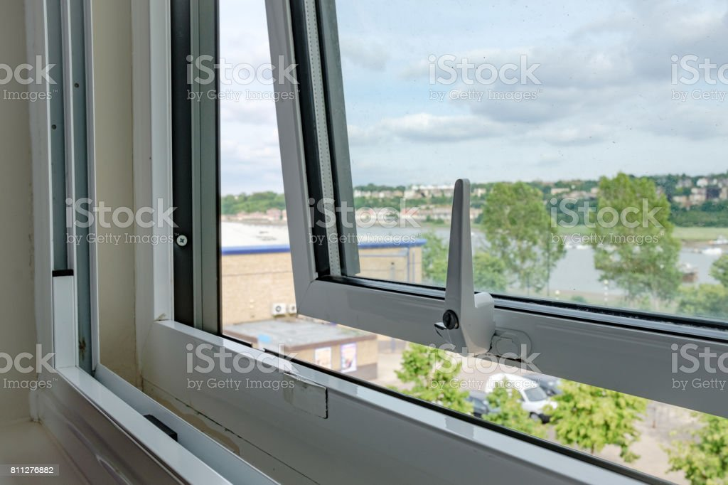 Apartment window shown opened to allow cool air in to the apartment room. stock photo