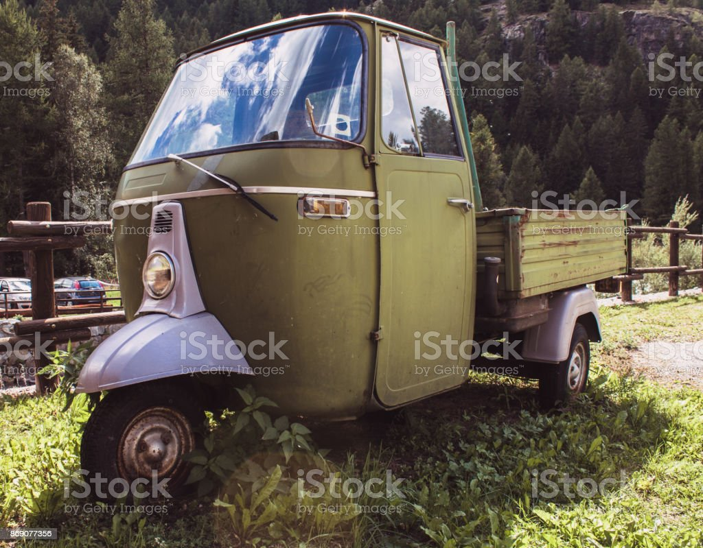 Ape car green framed from below in natural landscape - foto stock