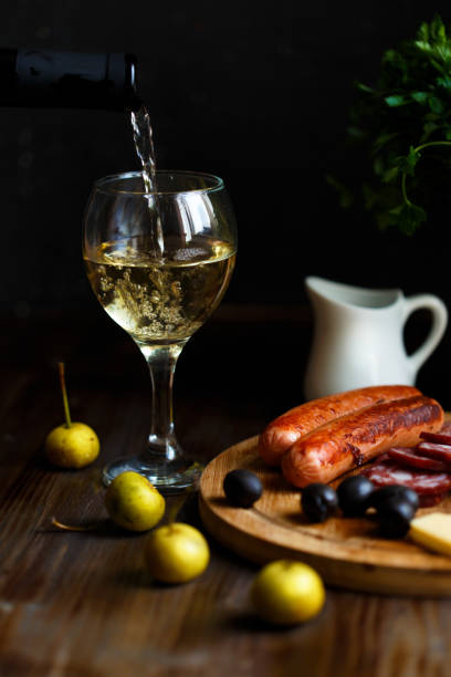 Aperitif concept. Wine pours into a glass goblet. On the table, meat appetizer, fried sausages, salami, cheese, olives. stock photo