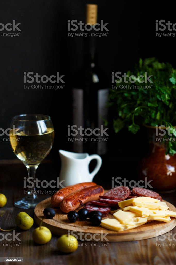 Aperitif table Meat snack, fried sausages, cheese, salami, olives and a glass of wine on a dark table Menu and restaurant concept stock photo