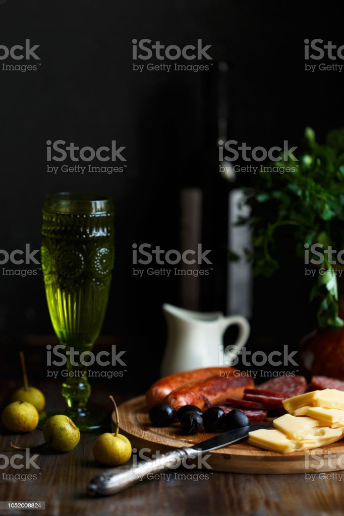 Aperitif table Meat snack, fried sausages, cheese, salami, olives and a glass of wine on a dark table stock photo