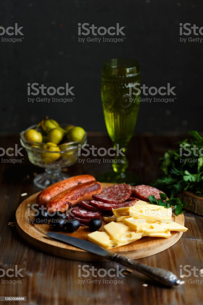 Aperitif table Meat snack, fried sausages, cheese, salami, olives and a glass of wine on a dark table. restaurant concept stock photo