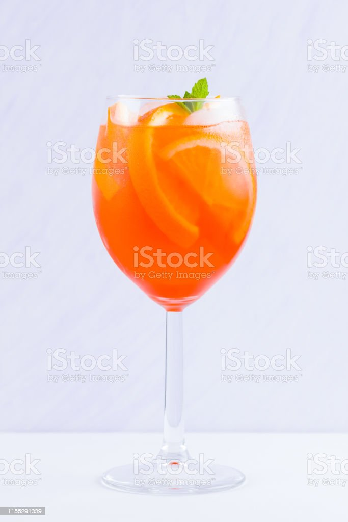 Aperol Spritz cocktail with mint leaves on a white background. A...