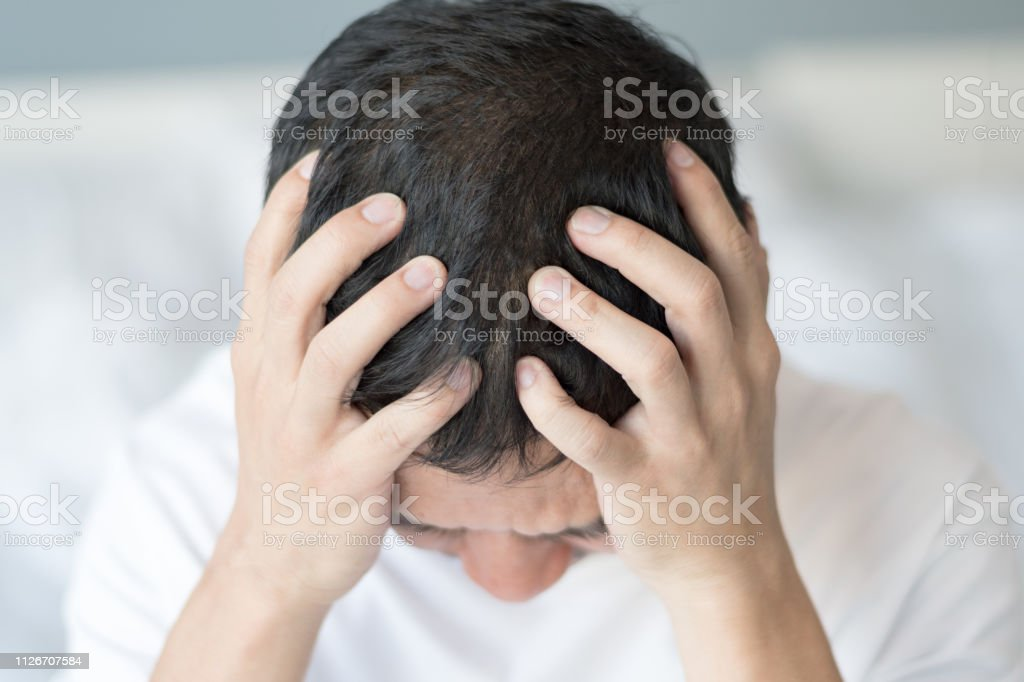 Aphasia awareness concept. business man in white t-shirt, hands on his head as headache migraine. Male adult look unhappy sad, tired and stressed out depressed, cannot figure out, having mental health problem trouble. stock photo