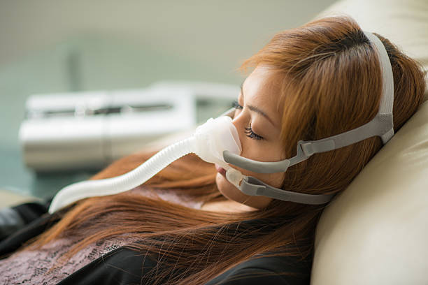 CPAP Apnea Medical Sleep close up picture of a asian young woman sleeping wearing an apnea mask on black background oxygen tube stock pictures, royalty-free photos & images