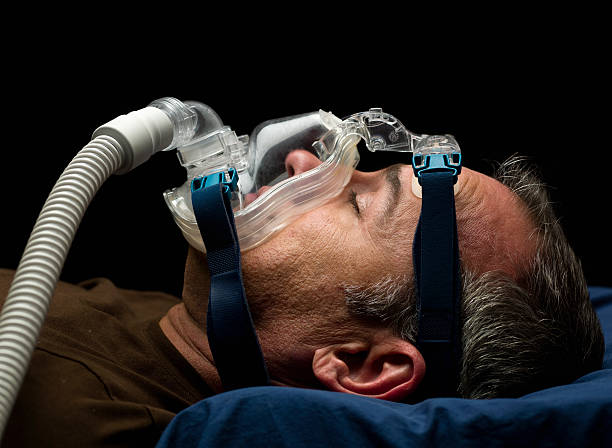 Apnea treatment mature man sleeping, using a mask for sleep disorder treatment (this picture has been taken with a Hasselblad H3D II 31 megapixels camera) oxygen mask stock pictures, royalty-free photos & images