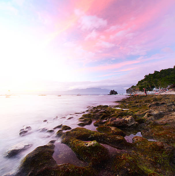 Apo Sunset over rocky coast of Apo island, Philippines apothegm stock pictures, royalty-free photos & images