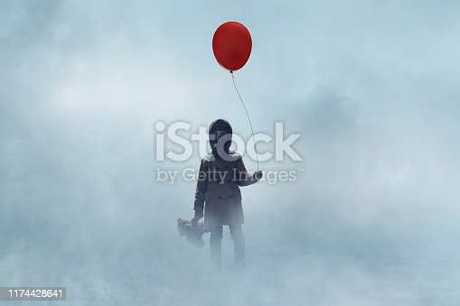 Little girl wearing gas and holding red balloon stands in fog