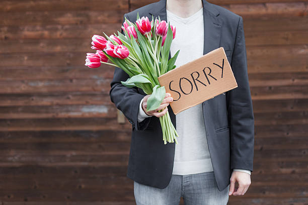 Apologize Man apologizing with flowers apologist stock pictures, royalty-free photos & images