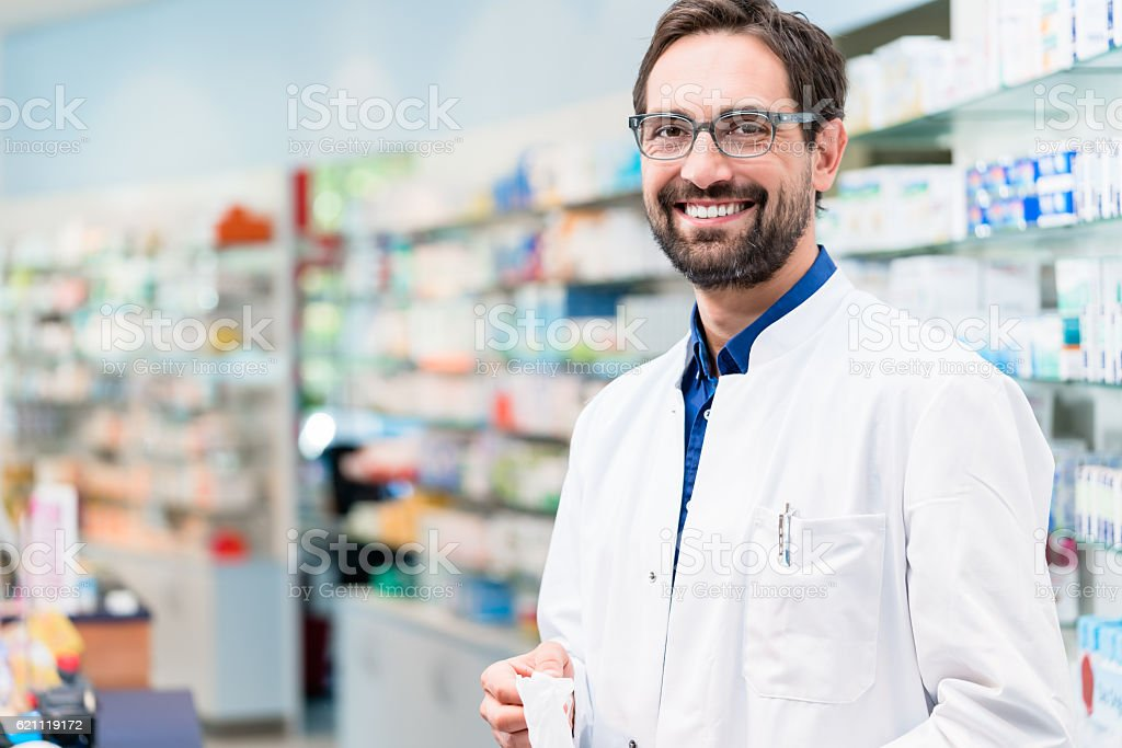 Apothecary in pharmacy standing at shelf with drugs – Foto