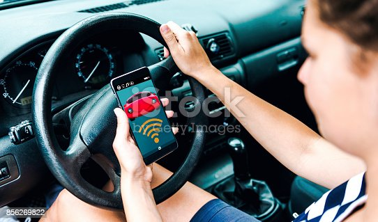 istock App controls parts of the car while woman sits at the steering wheel 856269822