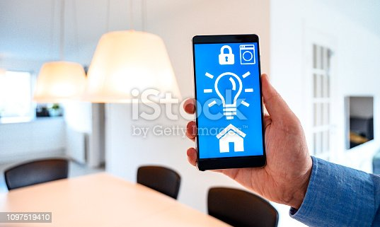 istock App on mobile phone controls light bulbs in smart home 1097519410