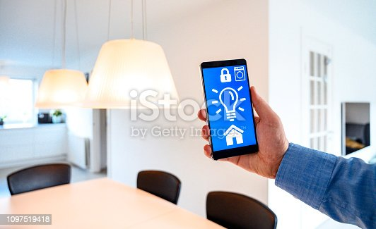 istock App on mobile phone controls light from lamps in smart home 1097519418