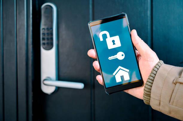 app on mobile phone unlocks electronic door lock in a smart home - intelligence стоковые фото и изображения