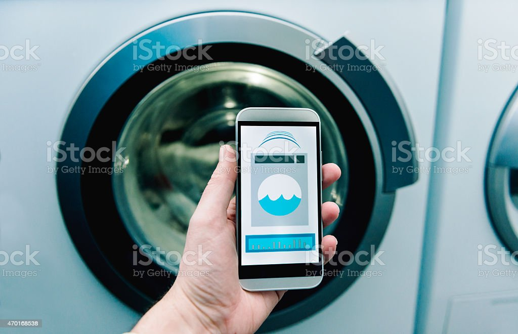 App on phone controls washing machine at home stock photo