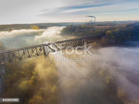 Sun rises over old railroad bridge and river while hydroelectric plant is visible in the background