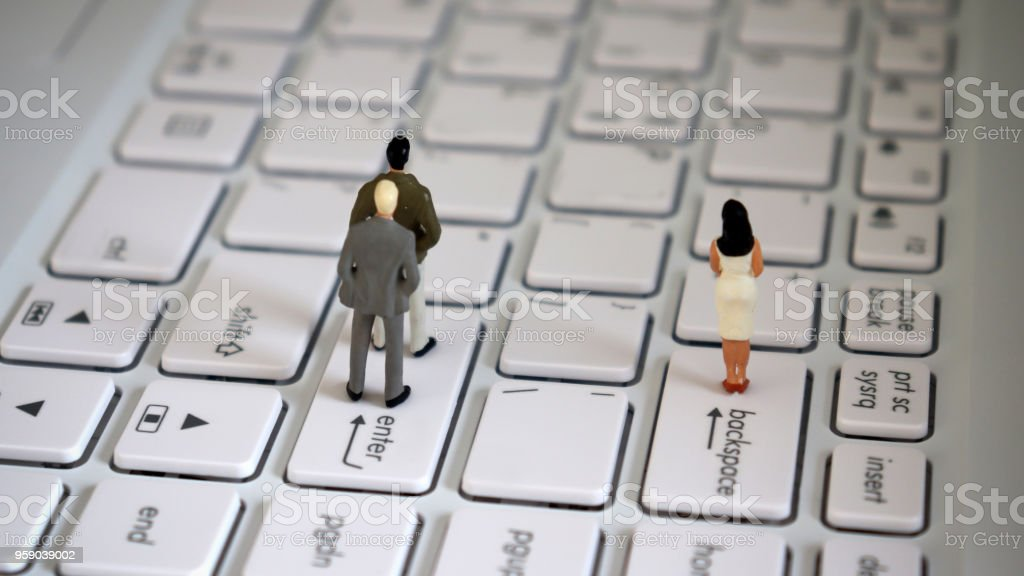 Appearance from behind of two miniature men standing on an enter key and a miniature woman standing on a backspace key. stock photo