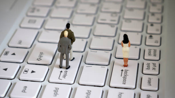 Appearance from behind of two miniature men standing on an enter key and a miniature woman standing on a backspace key. Appearance from behind of two miniature men standing on an enter key and a miniature woman standing on a backspace key. discriminatory stock pictures, royalty-free photos & images