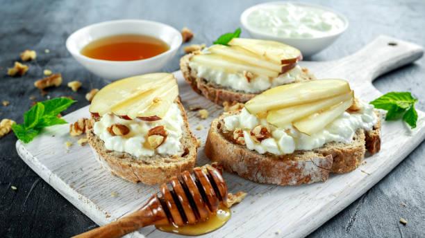 vorspeise-bruschetta mit birne, honig, walnuss und hüttenkäse auf weißen tafel. - ricotta stock-fotos und bilder