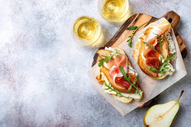 Vorspeise Crostini, Tapas, offene Sandwiches mit Birne, Schinken, Rucola und Blaukäse. Köstlicher Snack, Vorspeisen – Foto