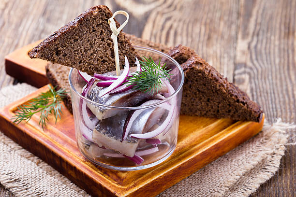 appetizer food, herring in a glass and rye bread - herring stock photos and pictures