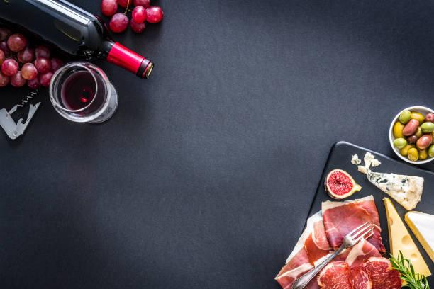 Vorspeiserahmen: Rotwein, schinken und Käse auf schwarzem Hintergrund – Foto