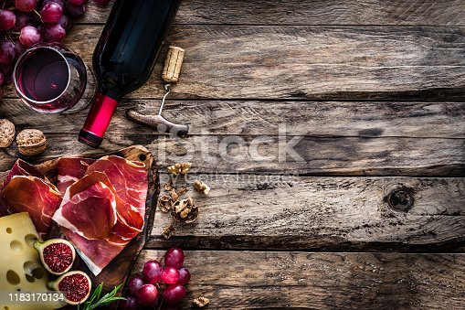 Appetizer: top view of a rustic table with a composition of red wine bottle, wineglass, a cutting board with cheese and Iberico ham and grapes arranged at the left border leaving useful copy space for text and/or logo at the right. Predominant colors are red and brown. XXXL 42Mp studio photo taken with Sony A7rii and Sony FE 90mm f2.8 macro G OSS lens