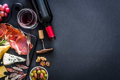 Appetizer: top view of a black background with a composition of red wine bottle, wineglass, a cutting board with various cheeses and Iberico ham arranged at the left border leaving useful copy space for text and/or logo at the right. Some grapes, olives, nuts and a corkscrew complete the composition. Predominant colors are red and black. XXXL 42Mp studio photo taken with Sony A7rii and Sony FE 90mm f2.8 macro G OSS lens