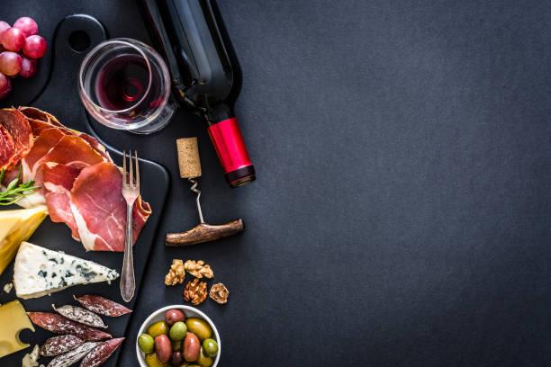 marco de aperitivo: vino tinto, jamón ibérico y queso sobre mesa rústica - cultura francesa fotografías e imágenes de stock