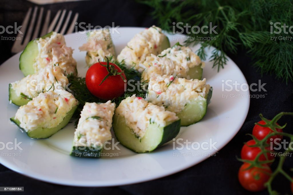 Appetizer from a fresh cucumber with crab meat, egg, cheese and dill. stock photo