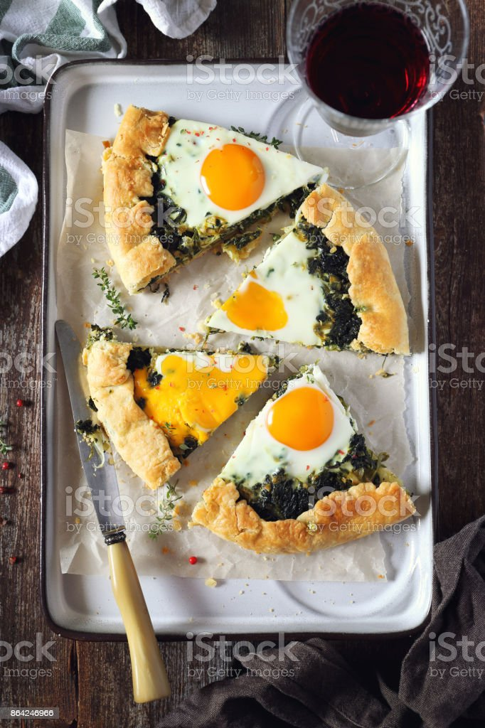 Appetizer, homemade spinach pie galette with eggs royalty-free stock photo