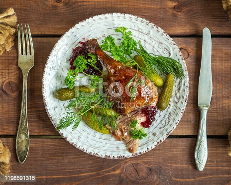 Appetizer of baked duck and fresh herbs on a round ceramic plate, serving on a wooden tray with Cutlery, close-up