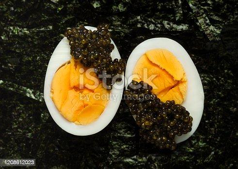 Appetizer of sturgeon caviar, half of boiled egg, shredded nori. Closeup view, horizontal orientation